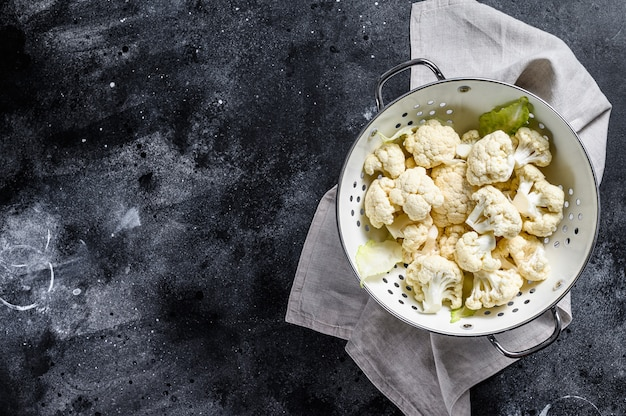 Fresh white heads cleaned cauliflower in a colander. black background. top view. copy space