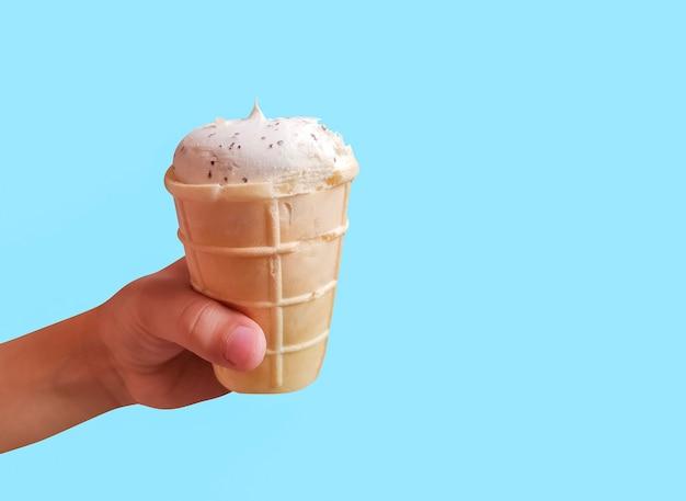 Свежее белое мороженое в вафельном стаканчике в руке ребенка на синем фоне