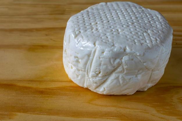 나무 판자 위에 분리된 신선한 흰색 미나스 치즈입니다.