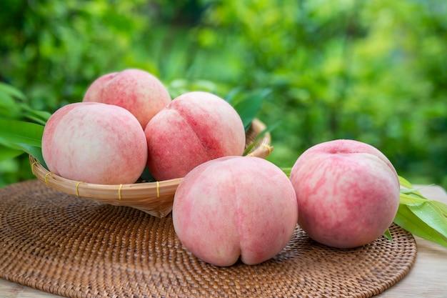 흐림 배경에서 신선한 화이트 복숭아 과일, 정원에서 나무 테이블에 대나무 바구니에 한국 백도.