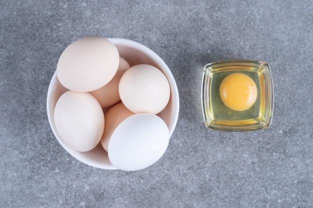 Свежие белые сырые куриные яйца на белой тарелке