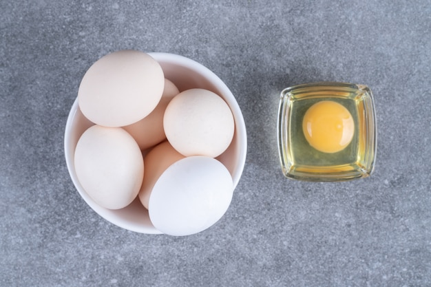 Uova di gallina crude bianche fresche su un piatto bianco