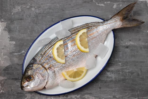 Fresh white seabream with ice and lemon on dish on ceramic background