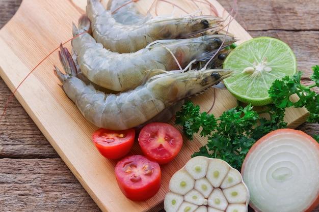 海鮮料理を作るために野菜とハーブを用意した、白いエビを見る