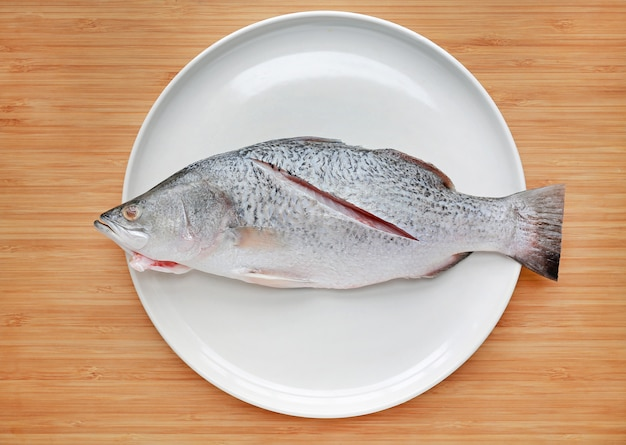 Fresh white snapper fish on white plate against wooden board background. raw food preparation on dish.