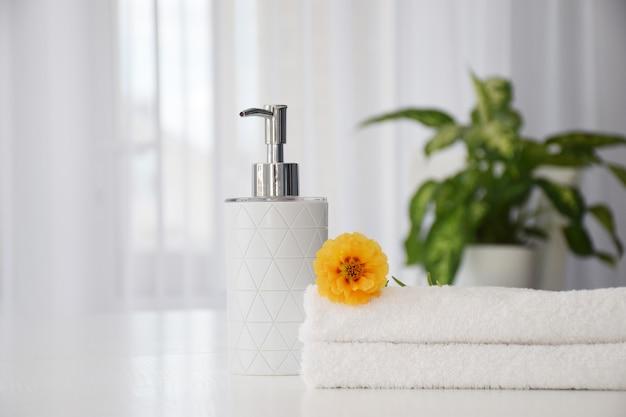 Свежие белые полотенца, сложенные на белом столе, оранжевом цветке и контейнере для жидкости с зелеными листьями комнатного растения и окном тюля на фоне. концепция химчистки или салона красоты.