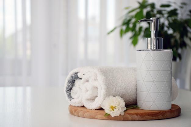 Свежие белые полотенца, сложенные на деревянной доске, белом цветке и контейнере для жидкого мыла с зелеными листьями комнатного растения и окном тюля на фоне. скопируйте пространство.