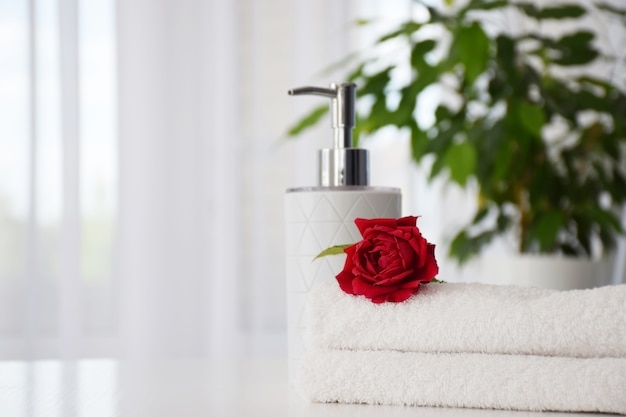 Fresh white towels folded on the table with red rose and hand soap dispenser with house plant