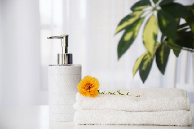 Fresh white towels folded on white table, orange flower and liquid container with green leaves of house plant and tulle window on background. dry cleaning or beauty salon concept.