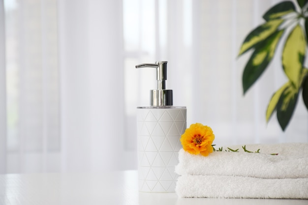 Fresh white towels folded on white table, orange flower and liquid container with green leaves of house plant and tulle window on background.
