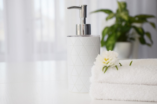 Fresh white towels folded on white table, white flower and liquid soap container with green leaves of house plant and tulle window on background. spa and wellness or beauty salon concept. copy space.