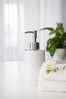 Fresh white towels folded on white table, white flower and liquid soap container with green leaves of house plant and tulle window on background