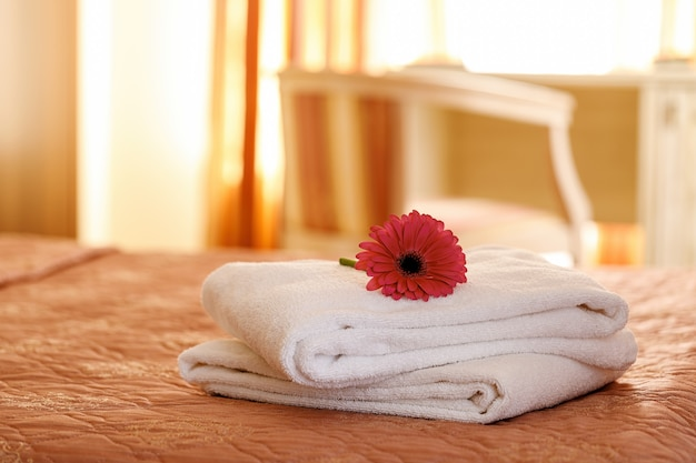 호텔 방의 침대에 꽃과 함께 신선한 흰색 수건. 장식.