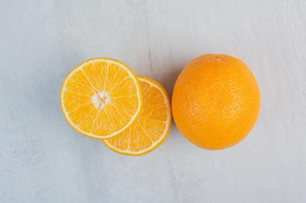 Свежие апельсины целиком и наполовину нарезанные на каменном фоне. фото высокого качества