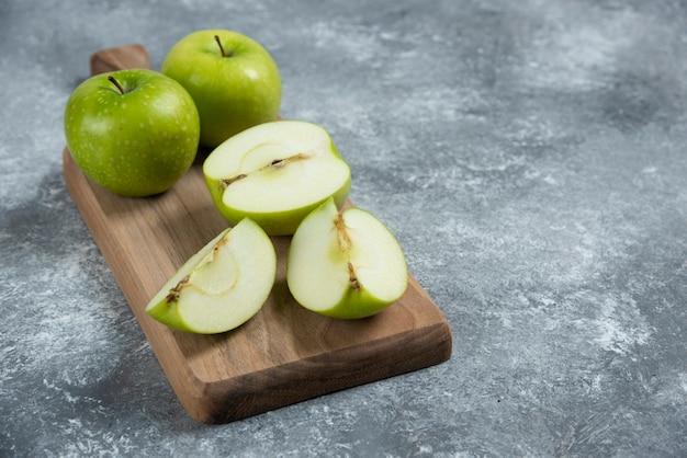 Свежие целые и нарезанные яблоки на деревянной доске.