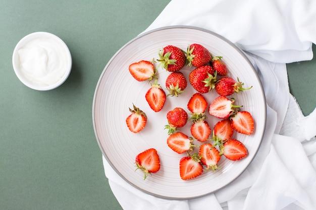 Свежая целая и нарезанная клубника на тарелке и сметана в миске на зеленом столе.