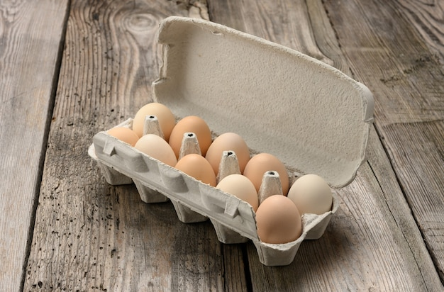 회색 나무 표면에 종이 포장에 신선한 전체 갈색 계란을 닫습니다.