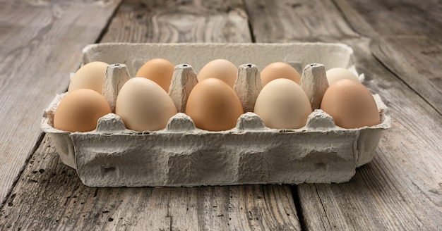 Свежие целые коричневые яйца в бумажной упаковке на сером деревянном столе крупным планом