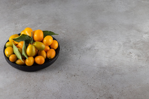 Fresh whole citrus cumquat fruits with leaves placed in bowl .