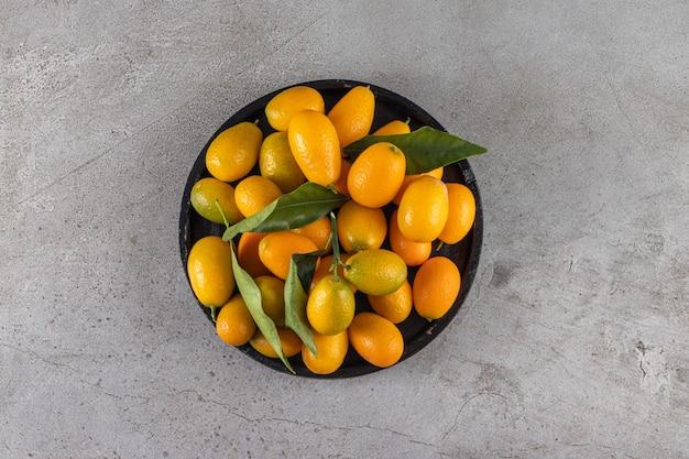 新鮮な丸ごと柑橘系のキンカンの果実と葉を黒いボウルに入れます。