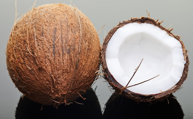 Fresh whole and half coconut on gray with reflection