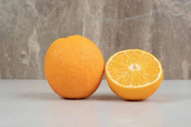 Arance fresche intere e tagliate a metà sulla tabella grigia