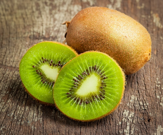 Fresh whole kiwi fruit and his sliced half on wooden background