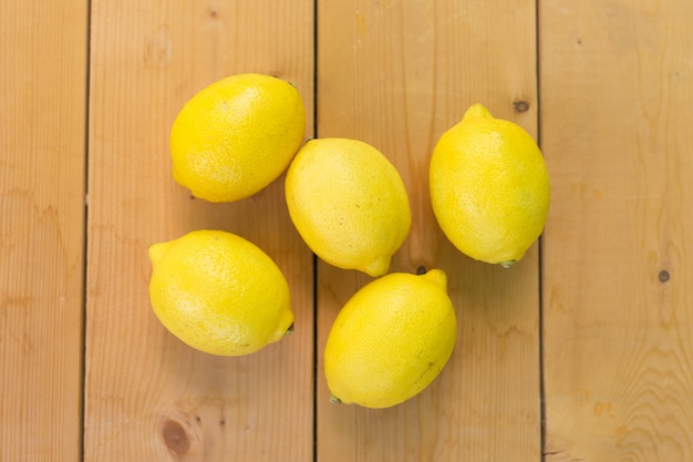 Fresh whole lemons on wooden table, flat lay, overhead. summer