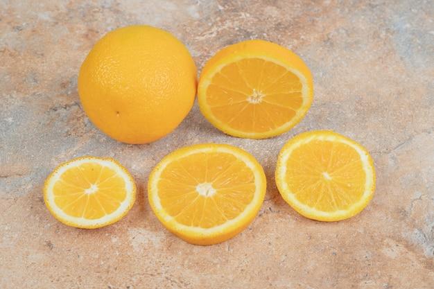 Arancia intera fresca e fette su fondo di marmo. foto di alta qualità