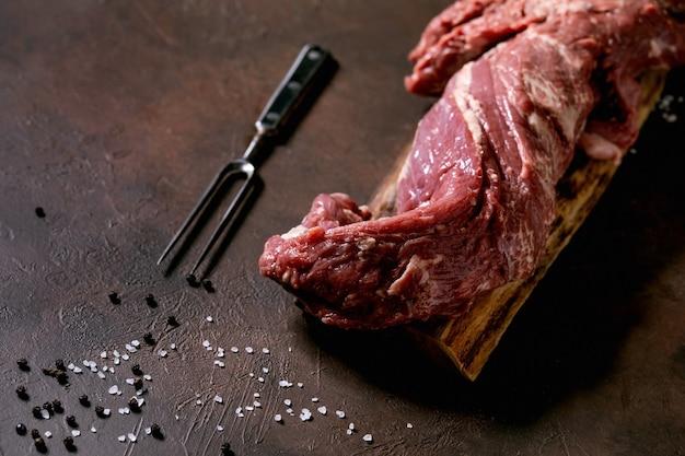 금속 고기 포크, 소금, 후추 어두운 갈색 질감 배경 위에 나무 보드에 신선한 전체 원시 쇠고기 안심 고기. 음식 요리 배경 개념입니다. 닫기, sapce 복사