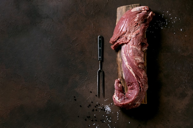 木の板に新鮮な丸ごとの生の牛ヒレ肉を、ダークブラウンのテクスチャー面に金属製の肉フォーク、塩、コショウを入れたもの。食品料理の背景コンセプト。トップ ビュー、フラット レイアウト、コピー スペース