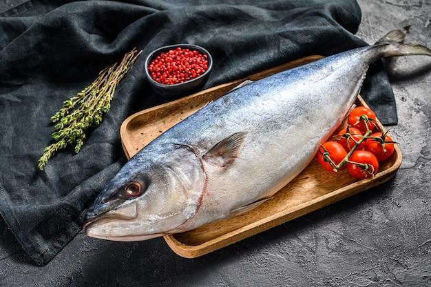 Свежий весь сырой японский желтохвост с помидорами и зеленью. рыба амберджек. черный фон. вид сверху.