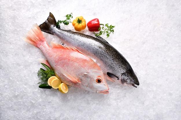 Свежий цельный лосось и красный окунь, морепродукты, сырые на льду