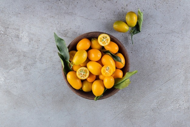 Fresh whole and sliced citrus cumquat fruits with leaves placed in wooden bowl