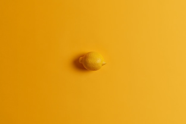 Fresh whole succulent juicy yellow lemon in one color with background. tropcial citrus fruit. monochrome shot. source of vitamins. ingredient for making lemonade. healthy food, eating concept