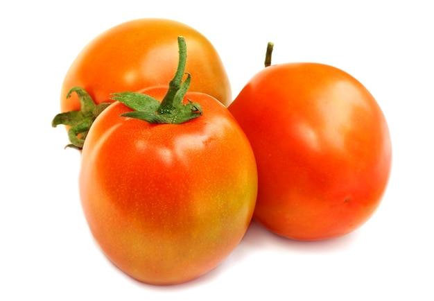 Свежие целые помидоры на белом фоне