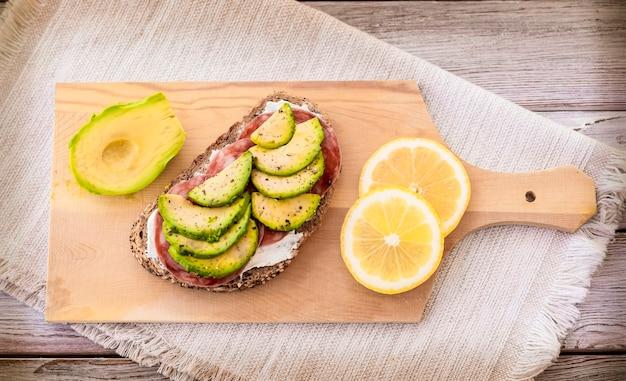 나무 커팅 보드에 치즈 살라미 소시지와 아보카도를 채운 신선한 통밀 샌드위치