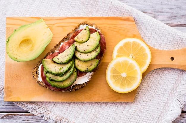 나무 커팅 보드에 치즈, 살라미 소시지, 아보카도 속을 채운 신선한 통밀 샌드위치