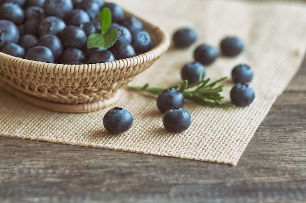 Fresh wild blueberries in wood basket on sack put on wooden table with copy space.