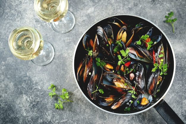 Fresh wild mussels in shells with green onions garlic parsley chili pepper white wine and olive oil