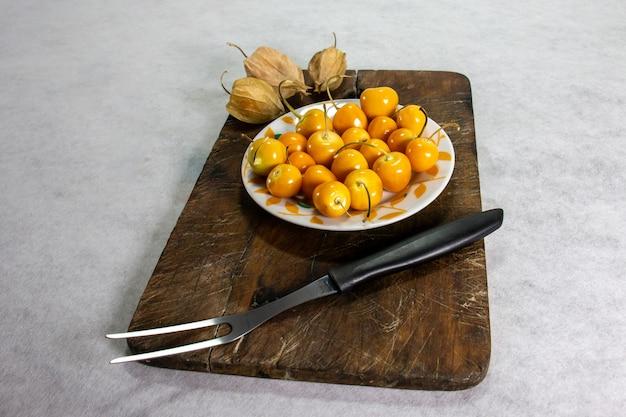新鮮な冬のサクランボphysaliscapeグーズベリーaguaymantouvilla皿の上とフォークの隣