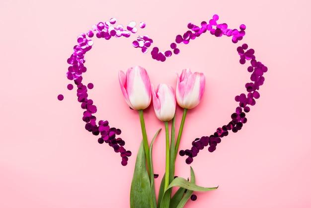 Fresh wonderful flowers in heart of confetti