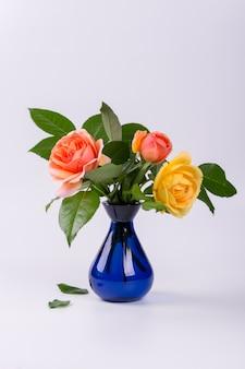 白い表面に分離された青い花瓶に新鮮な黄色と桃のバラ