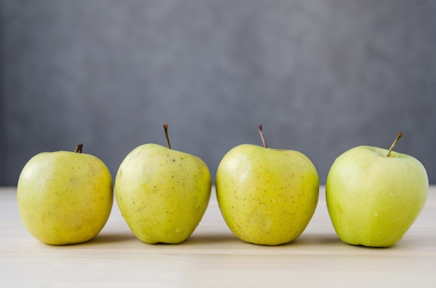 Fresh yellow apples on a wooden table