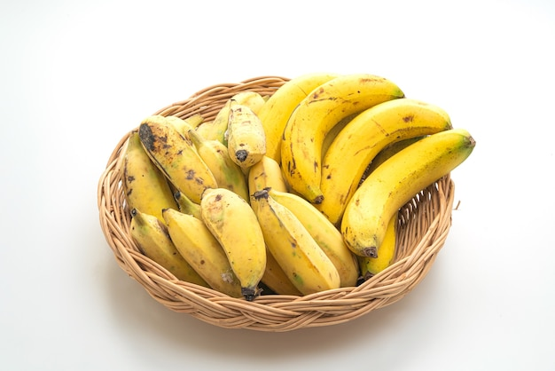 白で隔離のバスケットの新鮮な黄色のバナナ