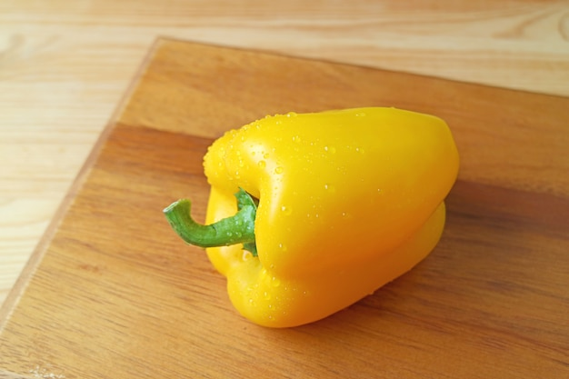 Fresh yellow bell pepper with water droplets isolated on wooden chopping board