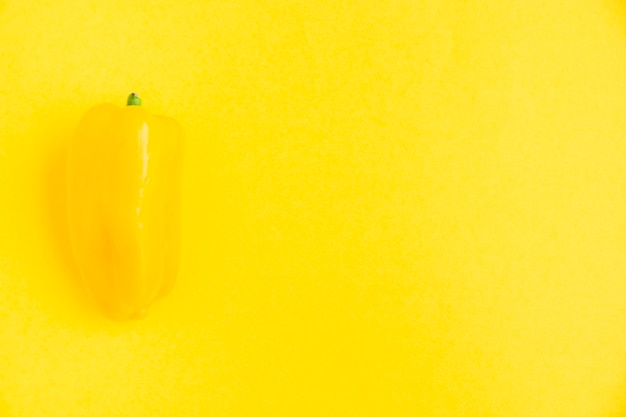 Fresh yellow bell pepper on yellow surface