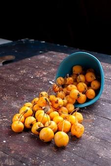 新鮮な黄色のサクランボは、茶色の木製の青いプレートの内側でまろやかでジューシーで、フルーツは熟している