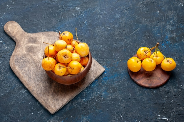 新鮮な黄色のサクランボは灰色がかった暗い机の上に熟した甘い果実、果実はまろやかな新鮮な甘いチェリー