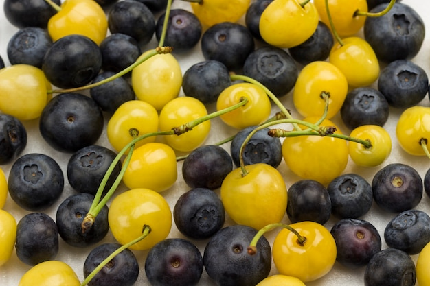 Fresh yellow cherry and blueberry on white surface